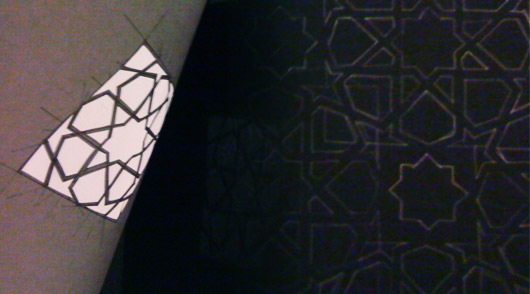 Using the new cut-out to trace a repeated/tiling pattern on to large black sheet of paper