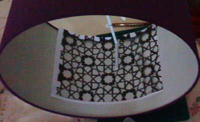 Placing the photocopied stencil within the lampshade to trace the pattern