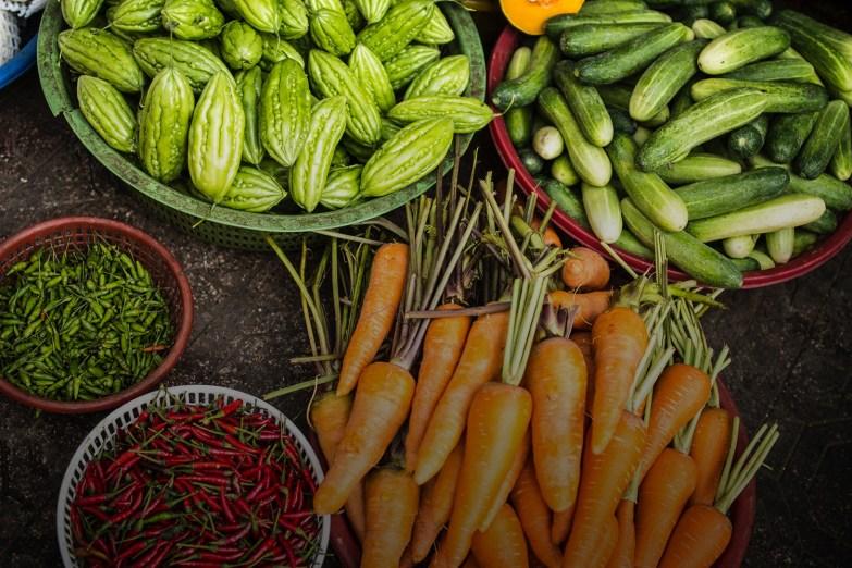 Cà rốt, dưa leo, mướp đắng, ớt xanh và ớt đỏ được bày trong các rổ ở chợ