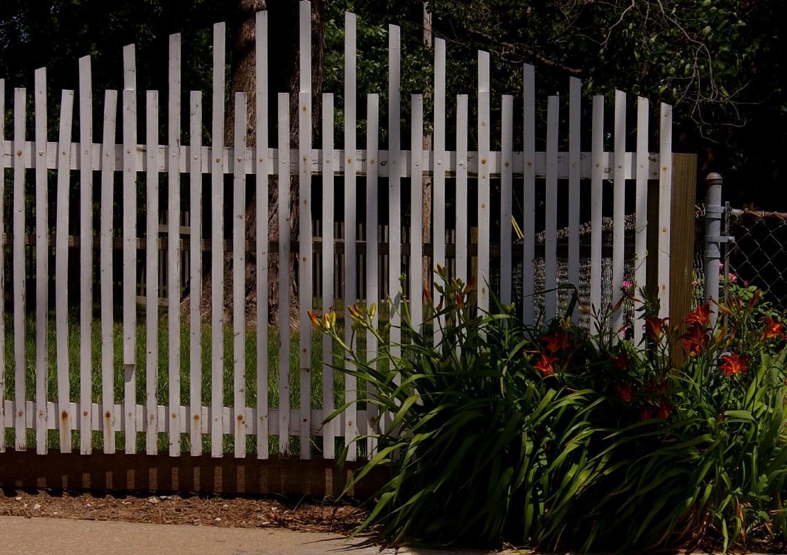 A white picket fence with some daylilies growing near the end