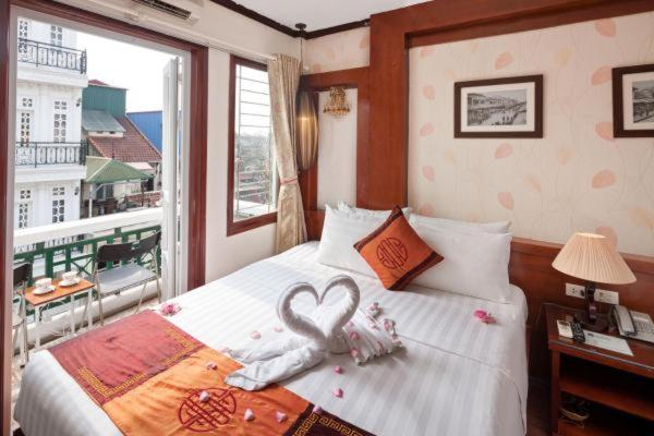 A bed or beds in a room at 7S Hotel Symphony Hanoi