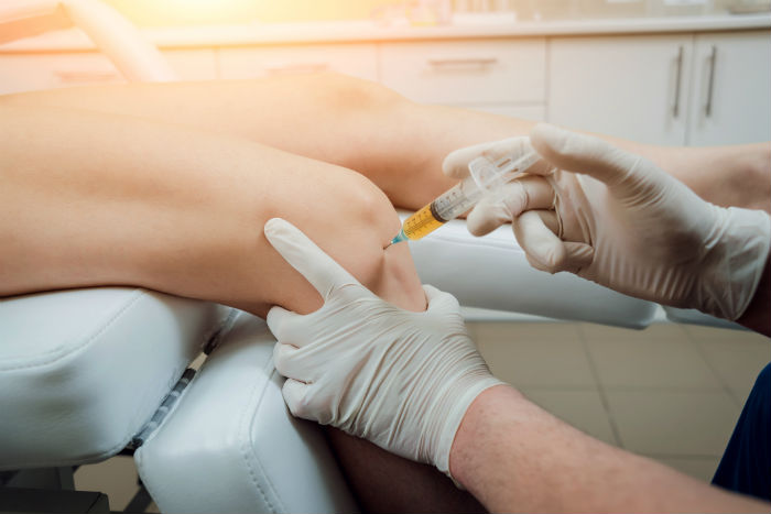 A doctor injecting a women's knee with platelet-rich-plasma
