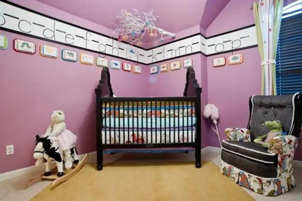 Cenário bonito e educacional nas paredes no quarto do garoto: grandes letras do alfabeto em molduras sob o teto