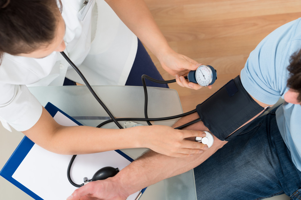 Close-up Of Female Doctor Checking Blood Pressure Of Male Patient