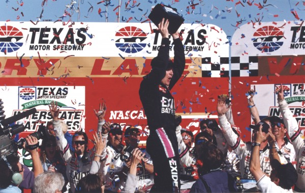 Jeff Burton, driver of the No. 99 Exide Batteries Ford, celebrates in Victory Circle by raising an Exide battery above his head while standing on his car following his victory in the Interstate Batteries 500, the inaugural NASCAR NEXTEL Cup Series (then Winston Cup Series) race at Texas Motor Speedway in Fort Worth, Texas on April 6, 1997. The win was also the first of Burton's Cup career.