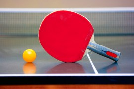 Ping pong ball and racket lying in the corner of the table