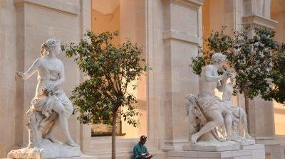 man in black jacket sitting beside statue of man