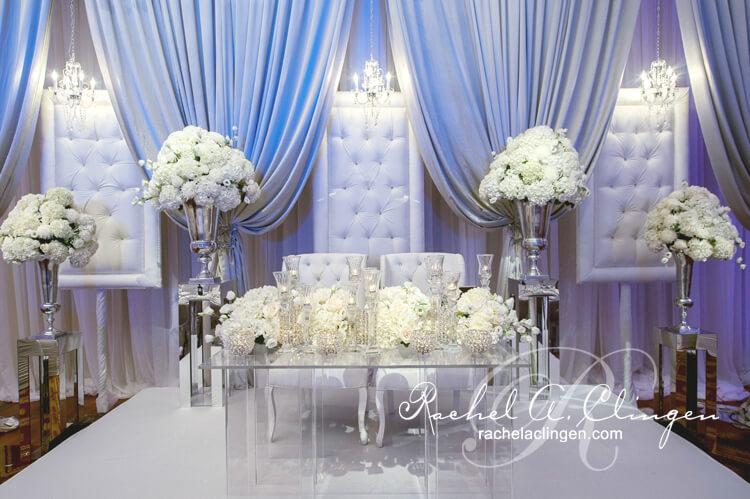 Lavish padded chairs and draped backdrop behind an elegant