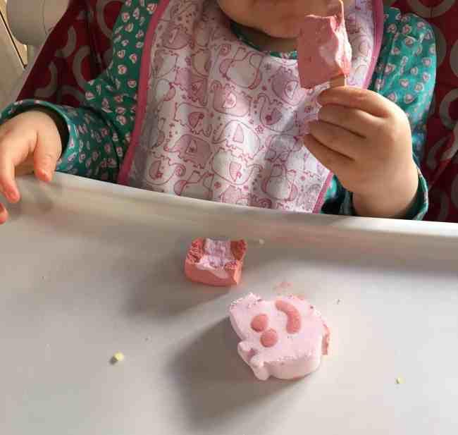 Baby girl eating peppa pig ice cream lollies