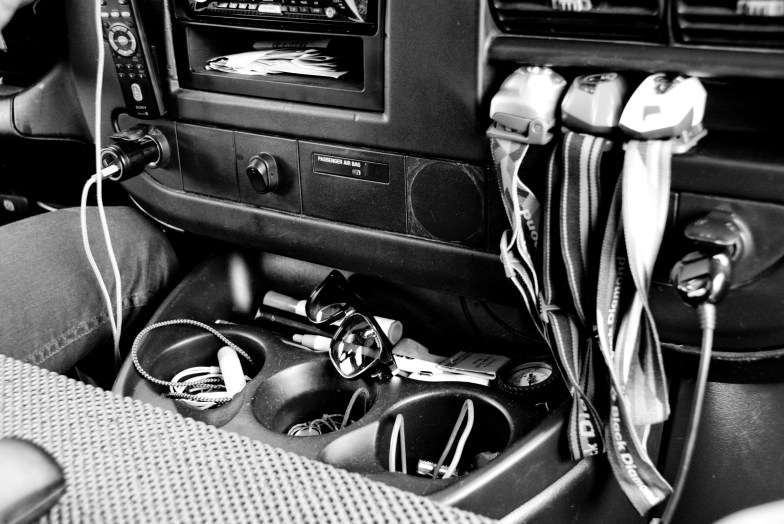 The front console holds some #vanlife necessities: various chargers, cords and hook-ups; compass; matches; sunglasses; multiple headlamps.