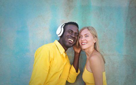 Black man sharing headphones with white woman