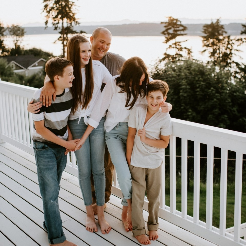 Gentle parenting family with their arms playfully around each other on the deck.