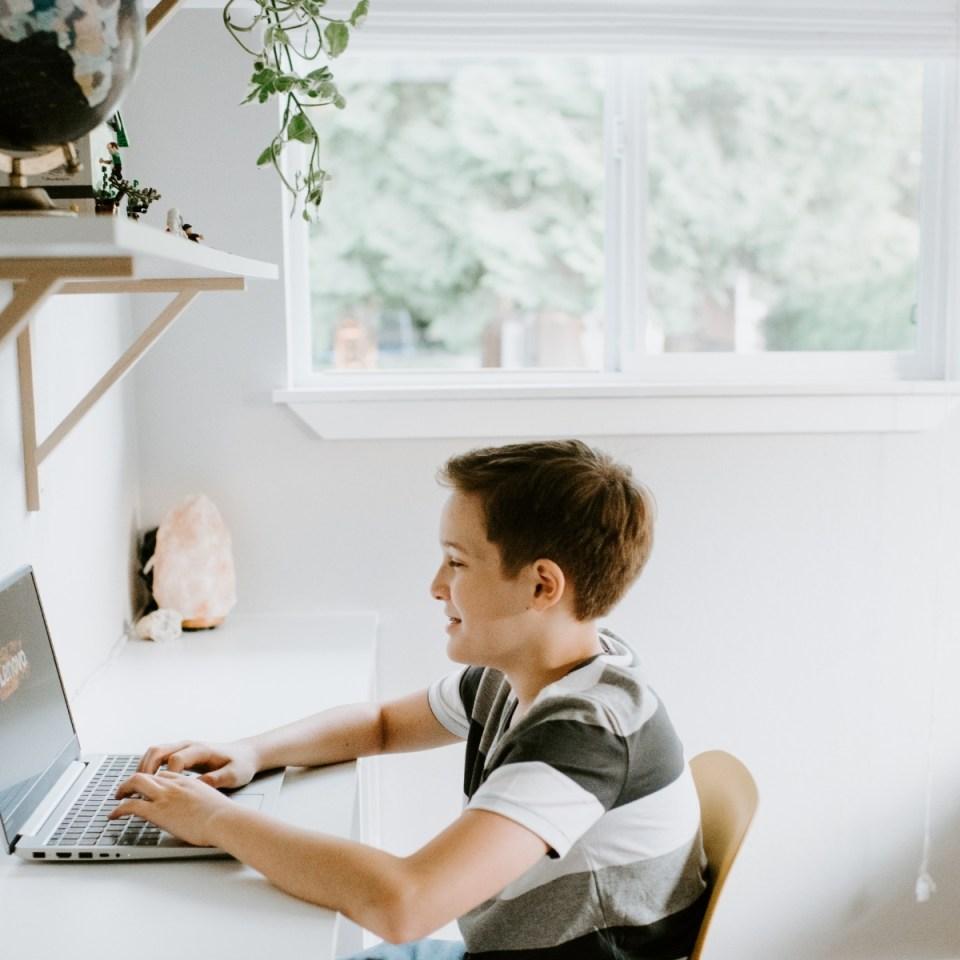 Tween boy doing homeschooling work at a desk in his minimalist bedroom.