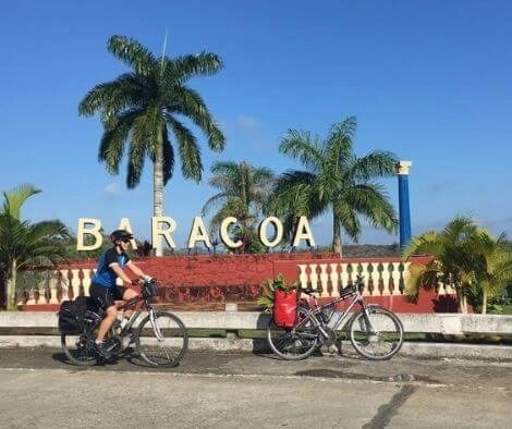 Two bicycles and Iszy before a sign for Baracoa