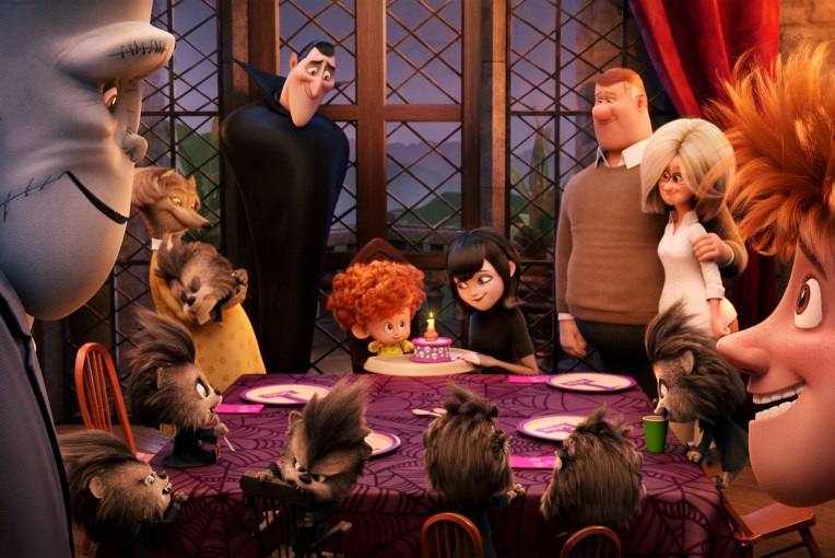 FILM STILL - HOTEL TRANSYLVANIA 2 - Frank (Kevin James and Jonathan (Andy Samberg) watch the birthday celebration of Dennis (Ashler Blinkoff, center) with Wanda (Molly Shannon), Dracula (Adam Sandler), Mavis (Selena Gomez), Mike (Nick Offerman) and Linda (Megan Mullally) in Columbia Pictures and Sony Picture Animation's HOTEL TRANSYLVANIA 2.