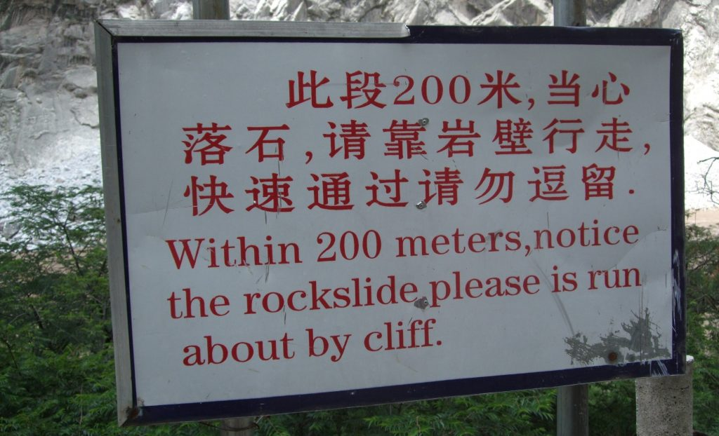 """sign reading """"Within 200 meters, notice the rockslide please is run about by cliff."""""""