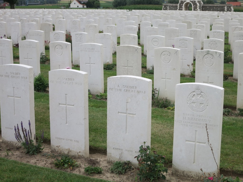 """Belgium war graves in Tyne Cot cemeteray. Rows of simple white gravestones. Most have a large crosee in the center. Many have a military insignia of some sort carved above that. Many just say """"A soldier of the Great War"""" in place of the insignia and then, below the cross, the words """"Known unto God."""" The nearest stone in the picture has a name: It reads """"29886 Private H. Bradbury East Lancashire Regiment 9th October 1917"""""""
