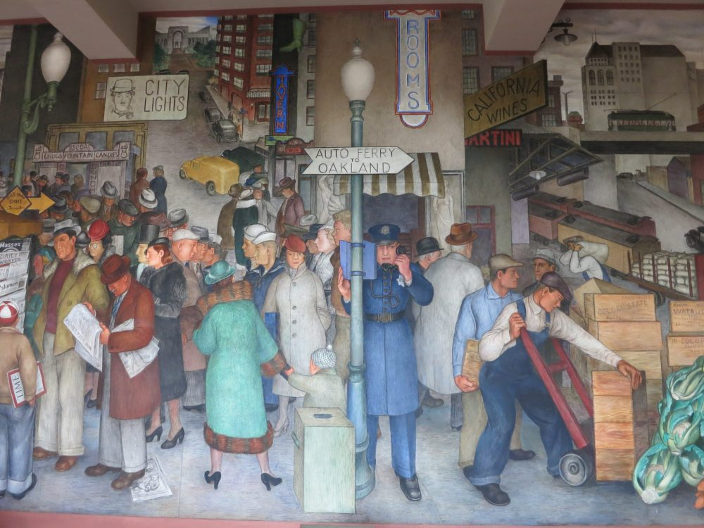 Coit Tower mural city scene: lots of people in 1930's clothing. ON the left some are reading a sign or reading a newspaper. IN the middle a woman holding a child's hand. A policeman speaks into a call box on a pole. ON the right, a worker uses a handcart to move crates. Sailors in the middle backgorund, advertising on the buildings: city lights (the film), rooms.