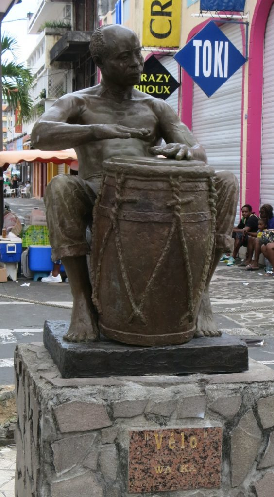 The statue showing a man playing a large drum