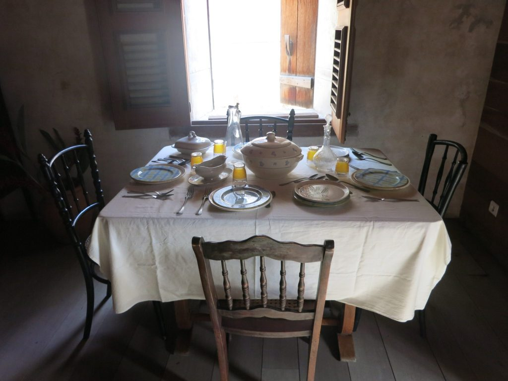The coffee plantation master's house interior view, showing a dining table with four chairs, all set for a meal