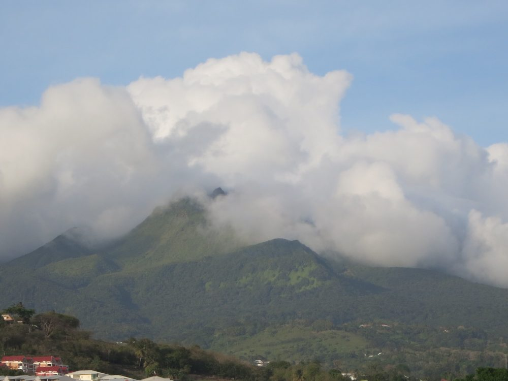 view of La Soufriere volcano from a distance. The sides of the mountain are covered in green, but the top is obscured by clouds.