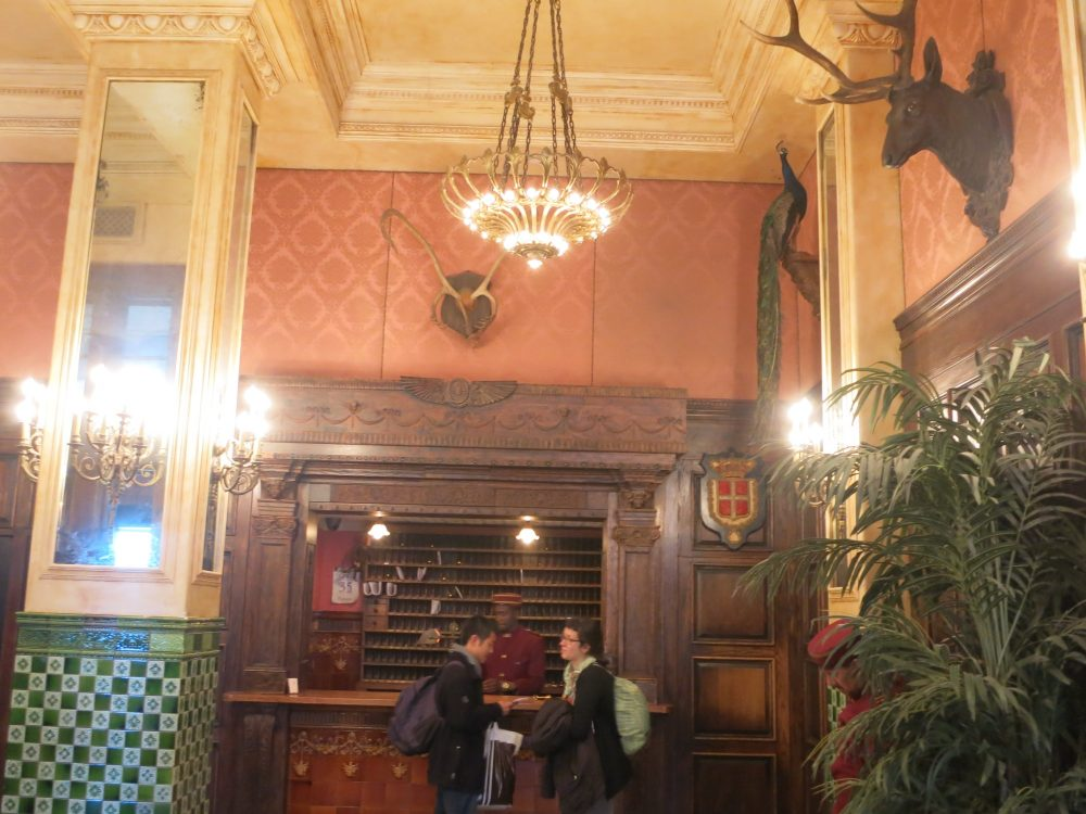the reception area of the Jane Hotel, showing stuffed animal heads and a stuffed peacock on the wall, and an employee in bellhop's uniform