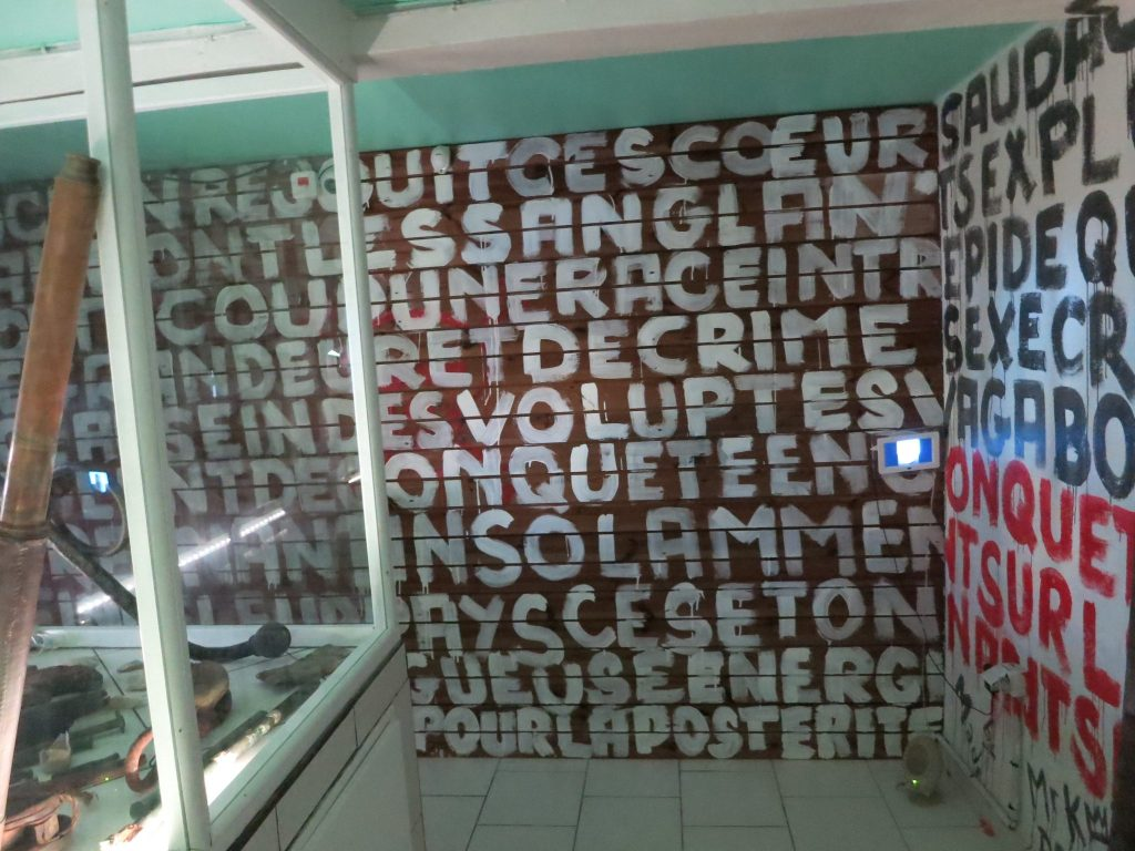 The wall is covered in closely-painted capitalized words in French: volupte, sanglant, etc. in the pirates room of Kreol West Indies