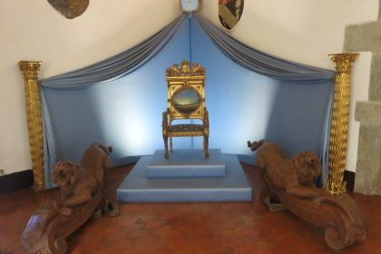 throne chair on a dais with a cloth draped above it in the Gala Dali museum