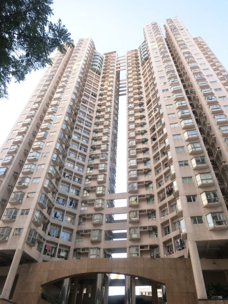 view looking up at an apartment building with two towers in Hong Kong. I think it's something like 28 stories tall. The towers are sort of cylindrical, but built so that each small apartment has windows on three sides and. The ones on the top several stories have bigger balconies.