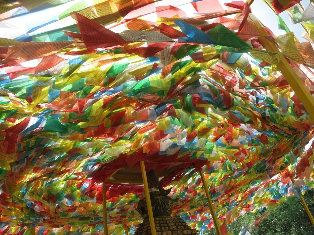 thousands of colorful flags waving at a shrine on Pulau Ubin