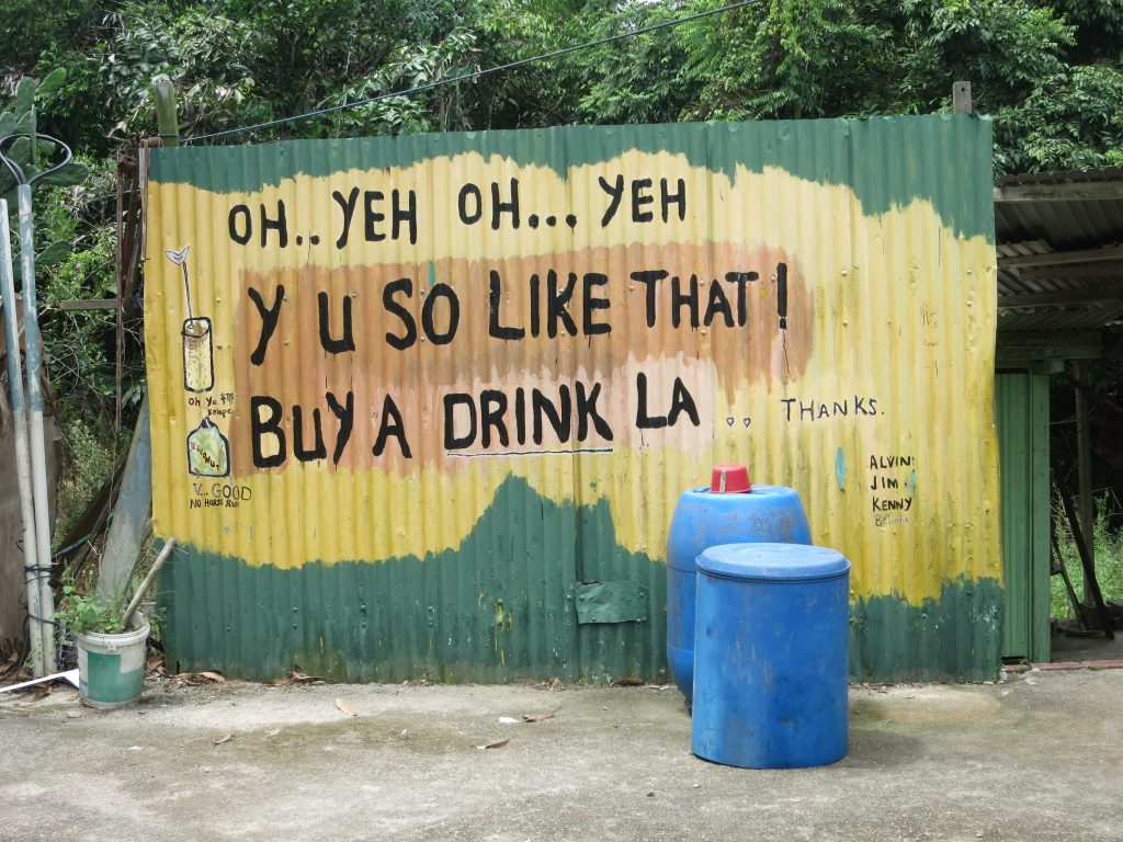 """a handpainted sign outside a drink stand on Pulau Ubin reads """"OH .. YEH OH ... YEH Y U SO LIKE THAT! BUY A DRINK LA."""""""