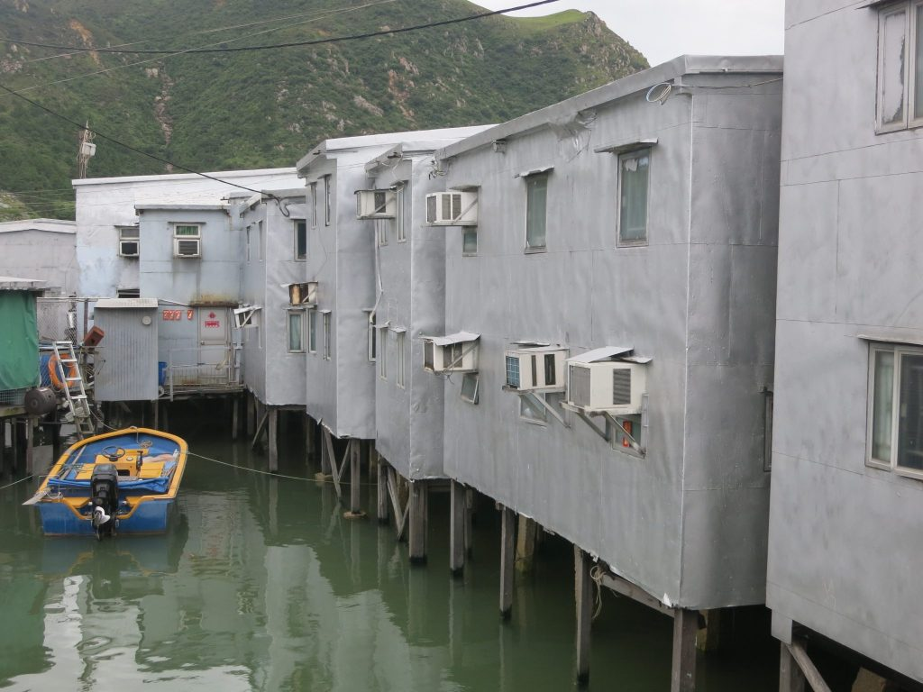 stilt houses, all painted grey, with airconditioners sticking out the windows, in Tai O
