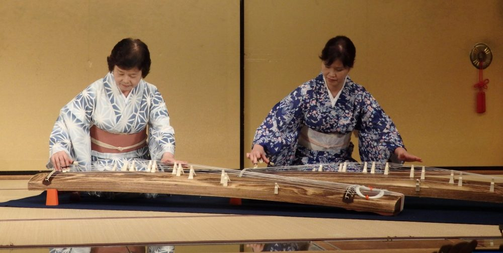 two women in kimonos sit on the floor, each playing a large harp that sits on the floor in front of them, in Gion Corner