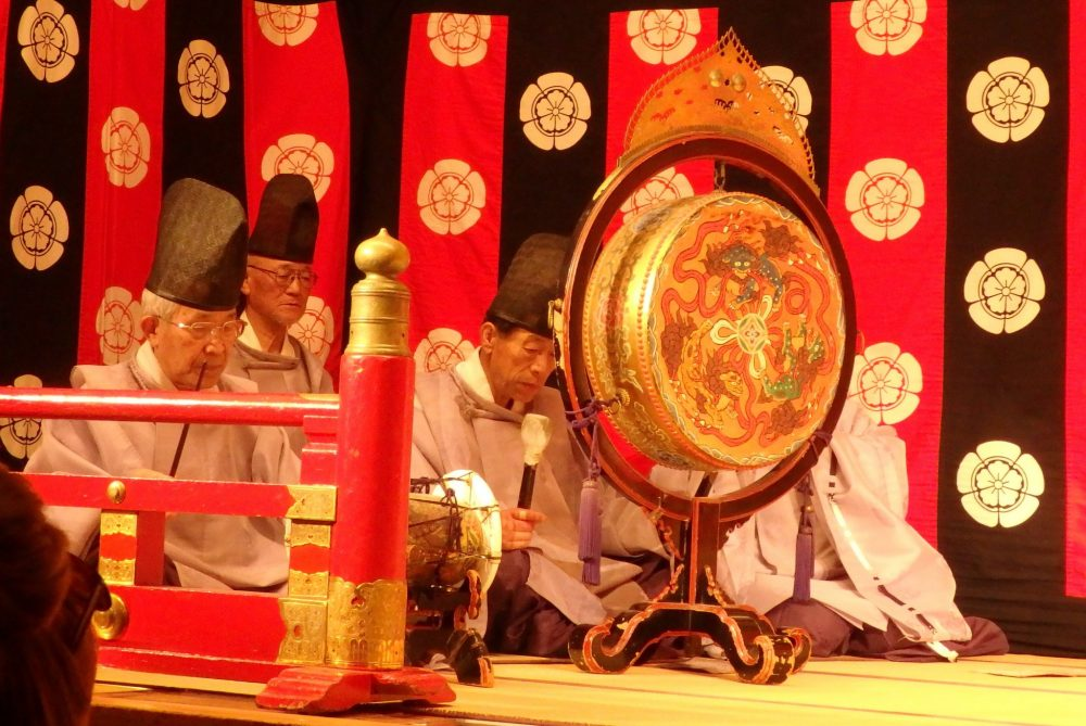 a group of men sit on the floor at the side of the stage. One bangs a large gone, while the others play other instruments, including flutes. Gion Corner