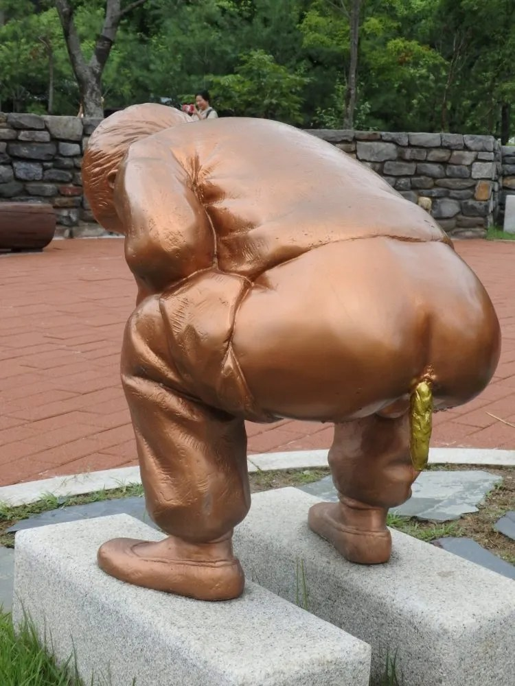 statue at the Toilet Museum in Sewon, South Korea, shows a man squatting with his pants down and golden poo coming out