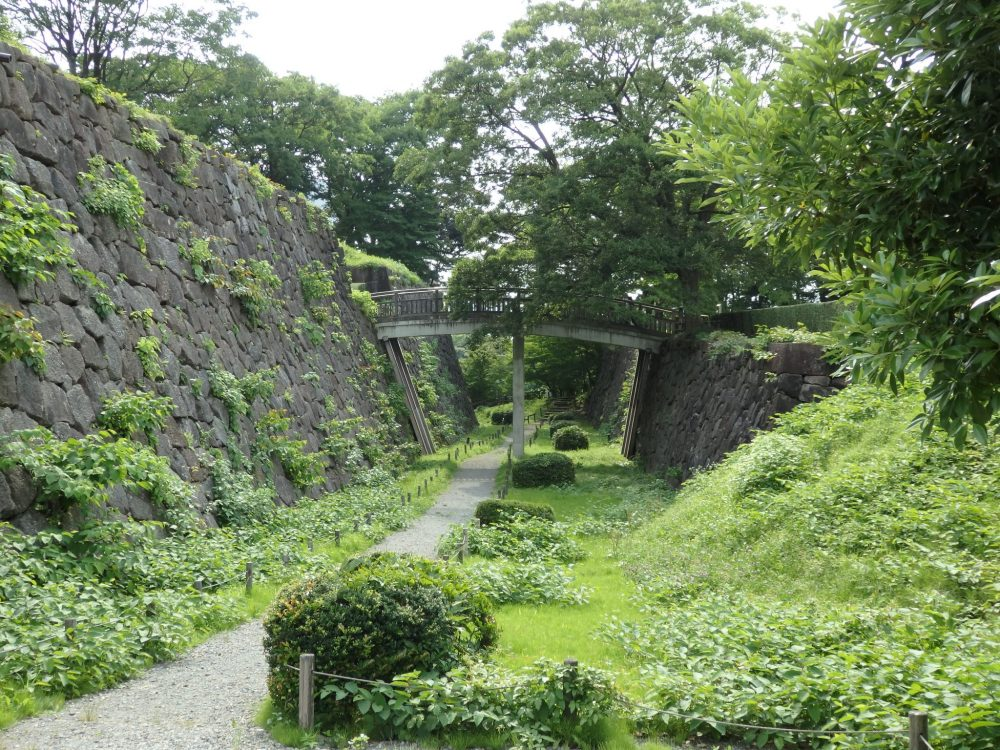 The moat has a grassy floor with a path running through it. On the left a steep, almost vertical wall of large stones. ON the right a grass-covered wall that is lower. A foodbridge connects the tops of both walls, crossing the path underneath.