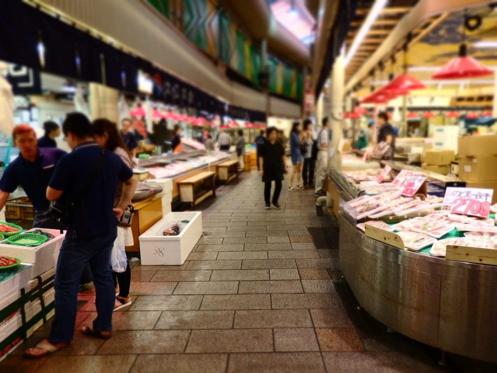 The seafood section of the market in Kanazawa. Looking down an aisle with stands on either side and a few customers shopping. Is Kanazawa worth a visit?