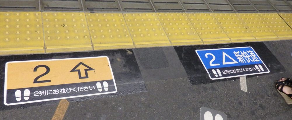 signs on the floor of the platform indicate where to wait. On the left, a yellow sign with an upward arrow and the number 2. On the right, a blue sign with a triangle and the number 2.