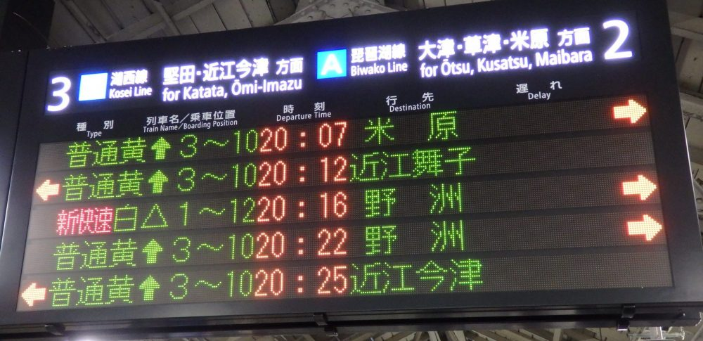 an electronic sign lists 5 trains, some arriving on the left-hand platform (marked as track 3 for Katata and Omi-Imazu) , some on the right (track 2 for Otsu, Kusatsu and Maibara). Next to 4 of them are upward arrows. ONe shows a triangle.