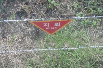"""This warning side by the side of the road near the DMZ reads simply """"MINE."""""""