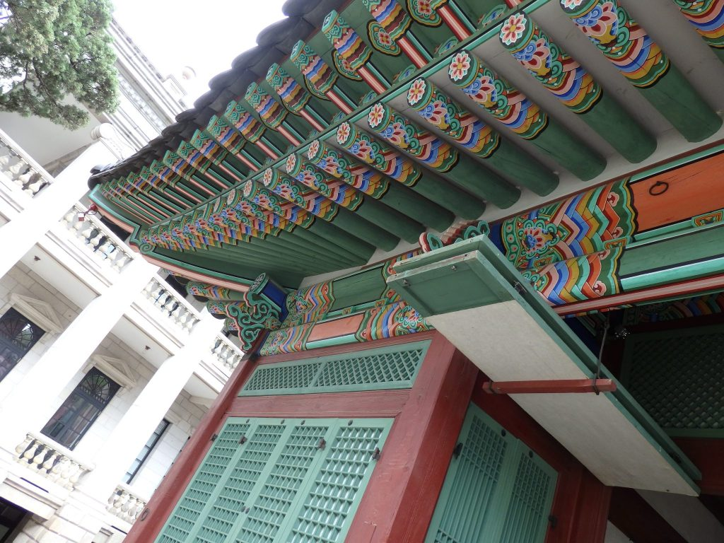 a building in traditional Korean style in the foreground; the neo-classical palace in the background, at Deoksugung Palace in Seoul, South Korea