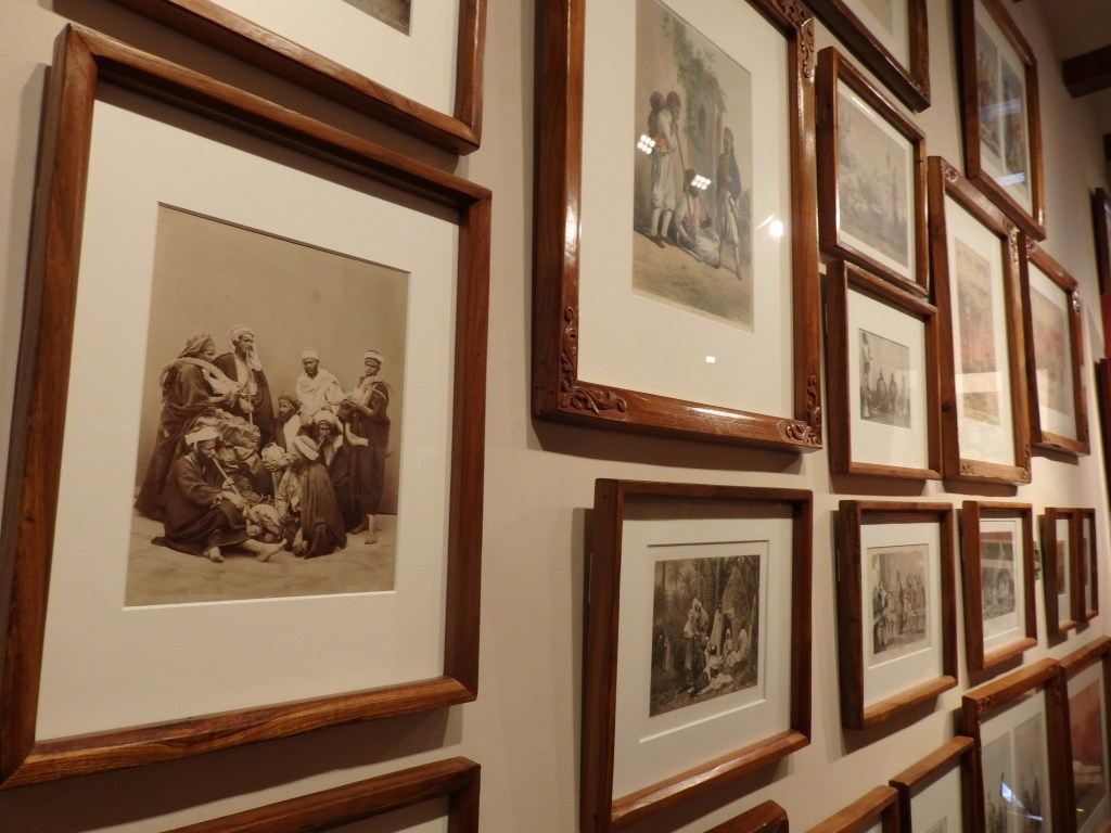 A section of one of the picture walls, this one showing antique photos and lithographs involving cannabis use