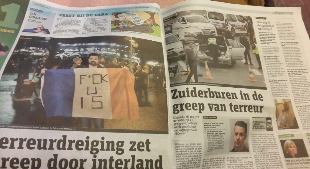 An open newspaper. Picture in the paper on the left has a man holding a French flag with the words F*CK U IS on it.