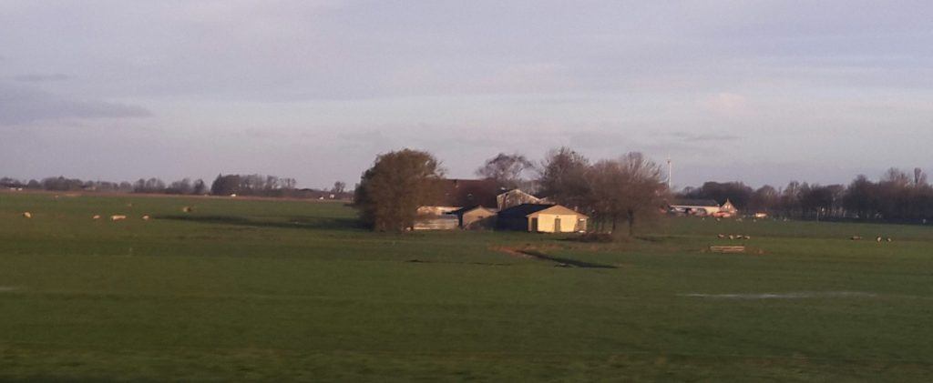 Farmland scene from the train window: a house with a barn, trees around it, surrounded by green fields.