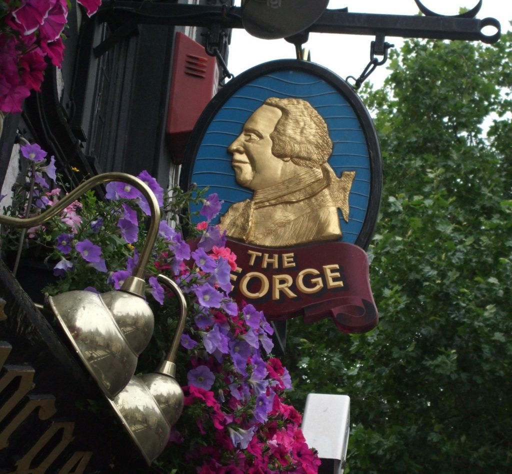 The sign for The George pub in London, surrounded by flowers.