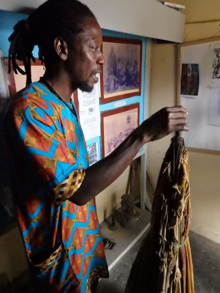 Simon shows us a large, cloth umbrella that a slave had to hold up over Abass's head at all times. Badagry, Nigeria