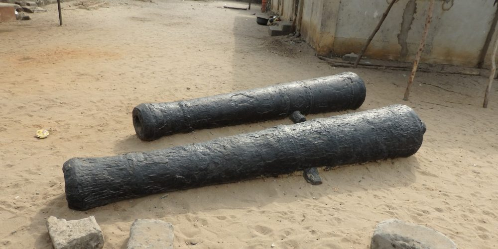two antique cannons in Badagry, Nigeria, just lying on a sandy piece of ground.