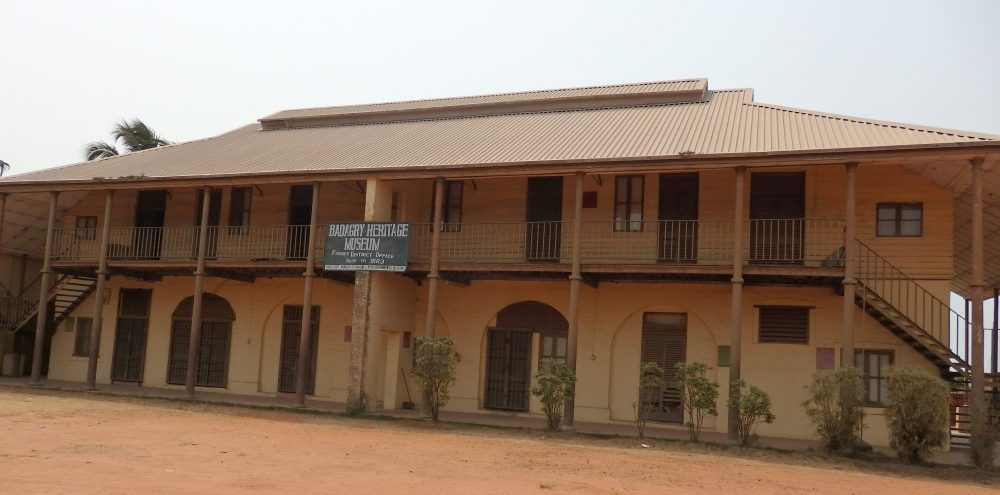 """A wide, low building of two stories, with the roof extending forward over a balcony that runs the entire length of the building. Along both shaded floors are several doorways and, on the ground floor, two archways as well. A sign in the middle reads """"Badagry Heritage Museum."""""""