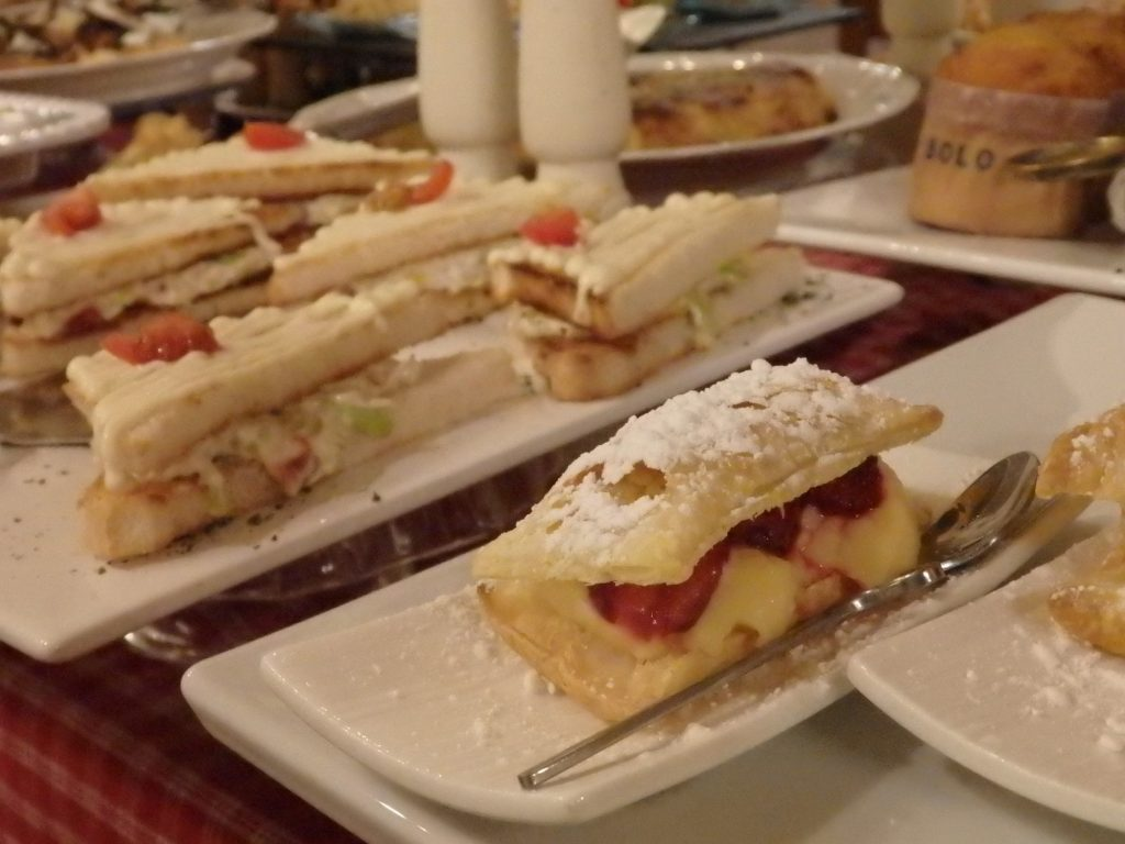 a cream-filled baked item, in front of a sandwich of some sort, with more baked goods in the background, at Hotel El Ciervo