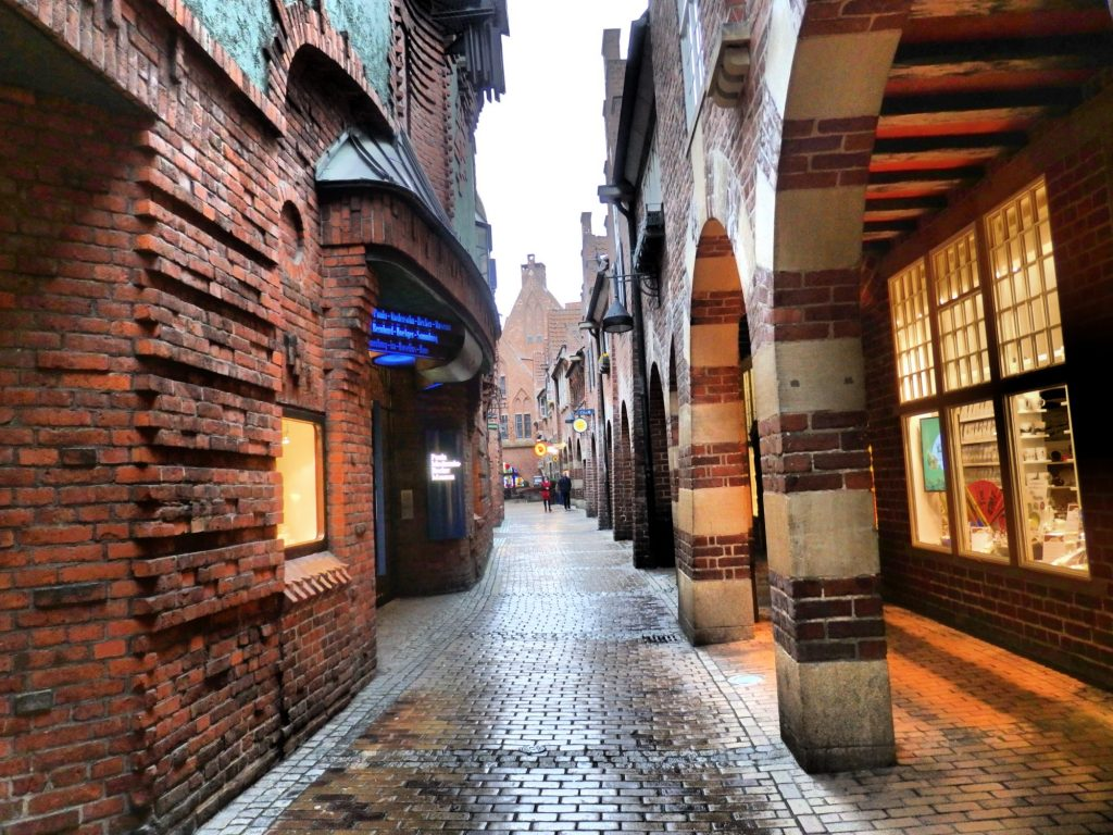 On the right is an arcade with arched columns in alternating red brick and concrete. ON the right is a red-brick building with interesting patters to the brick: sometimes protruding, sometimes not, forming circles and arches in the facade. The street ahead is brick paved.